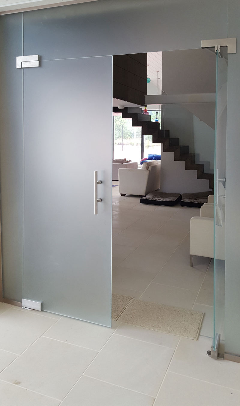 frameless glass partition with hinged doors and privacy glass