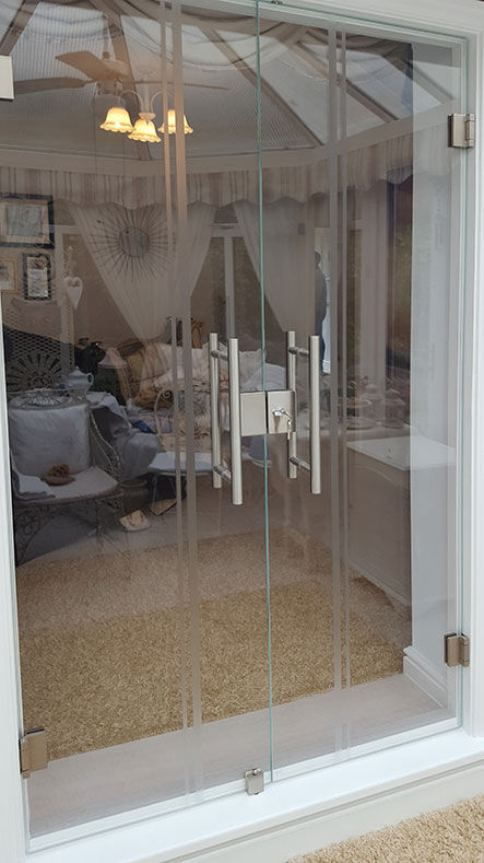 full glass doors in timber surround with pull bars and lock