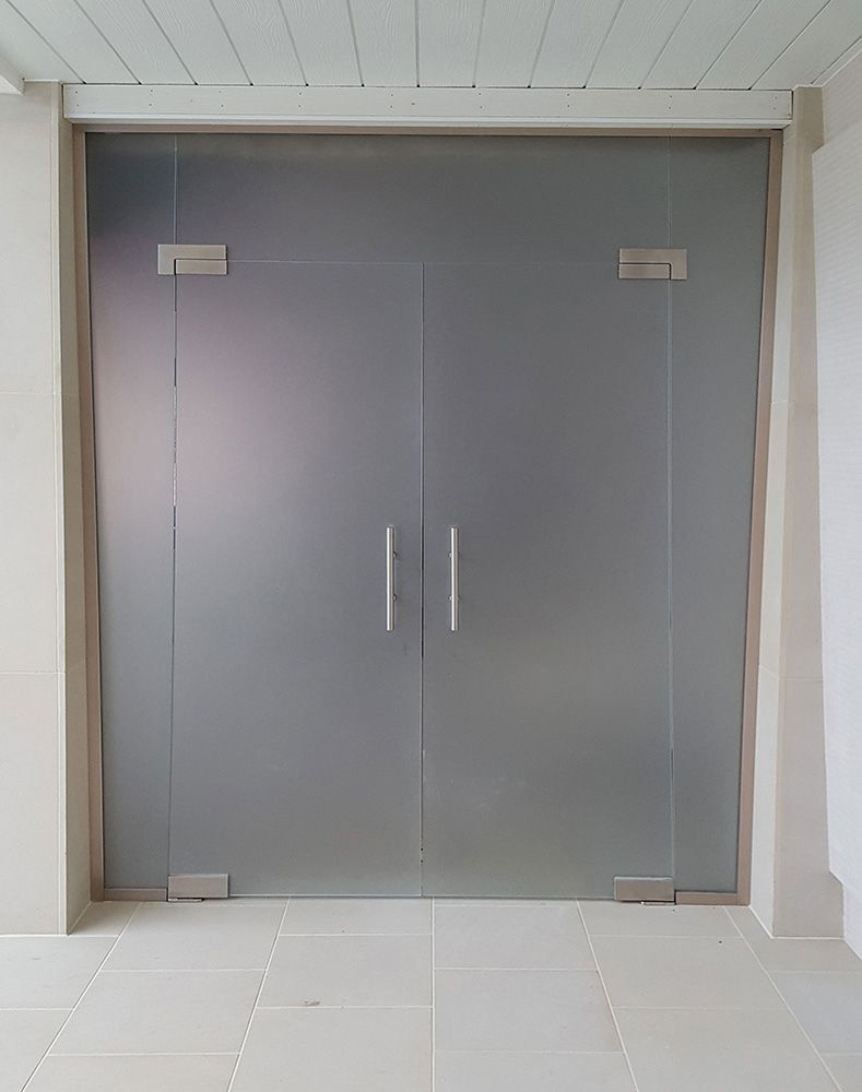 frameless glass partition with hinged doors and satin glass